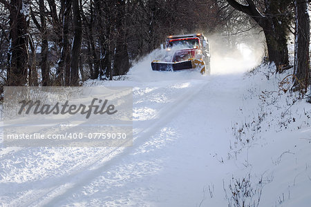 A snowplow truck removing snow from a tree lined rural road on a cold winter day. Stock Photo - Budget Royalty-Free, Image code: 400-07759030