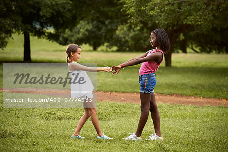 Two hispanic and african little girls playing ring around the rosie in public park and holding hands Stock Photo - Budget Royalty-Free, Image code: 400-07774033