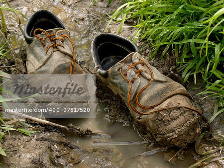 muddy worn out shoes in the puddle Stock Photo - Budget Royalty-Free, Image code: 400-07817520