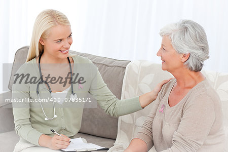 Doctor talking with her patient wearing breast cancer awareness ribbon Stock Photo - Budget Royalty-Free, Image code: 400-07835171