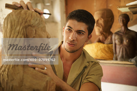 Man, people, job, young student at work learning craftsman profession in art class, working with wooden statue and carving wood Stock Photo - Budget Royalty-Free, Image code: 400-07899762