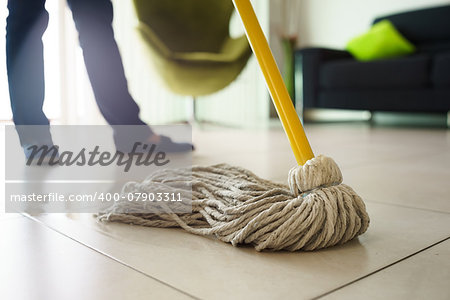 Woman at home, doing chores and housekeeping, wiping floor with water in living room. Focus on floor and mop Stock Photo - Budget Royalty-Free, Image code: 400-07903311