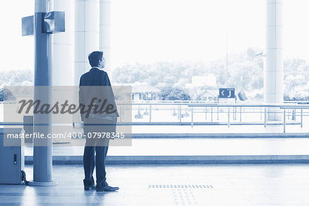 Rear view full body Asian Indian business man waiting bus at public bus station, in blue tone. Stock Photo - Budget Royalty-Free, Image code: 400-07978345