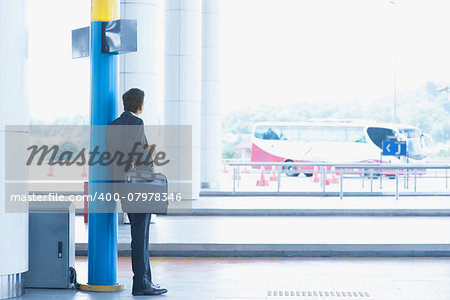 Rear view full body Asian Indian business man waiting bus at public bus station. Stock Photo - Budget Royalty-Free, Image code: 400-07978346