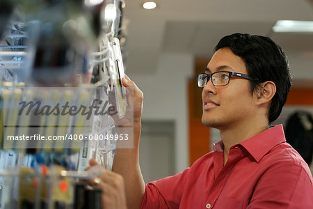 Chinese sales clerk working in computer store, arranging and ordering cables and usb flash memory drives on shelf Stock Photo - Budget Royalty-Free, Image code: 400-08049953