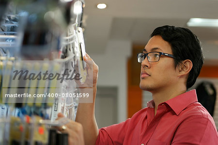 Chinese sales clerk working in computer store, arranging and ordering cables and usb flash memory drives on shelf Stock Photo - Budget Royalty-Free, Image code: 400-08051599