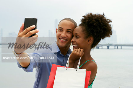 Black tourist heterosexual couple in Casco Antiguo Panama City with shopping bags. The man takes a selfie with his girlfiend and shopping bags with skyline in background Stock Photo - Budget Royalty-Free, Image code: 400-08054733