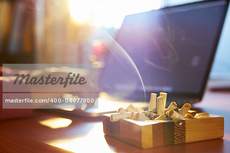 Close up of ashtray full of cigarette, with man in background working on laptop computer and smoking indoors on early morning. Concept of addiction and abuse of nicotine. Stock Photo - Budget Royalty-Free, Image code: 400-08077800