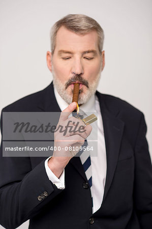 Male entrepreneur lighting up a cigar with lighter Stock Photo - Budget Royalty-Free, Image code: 400-08109564