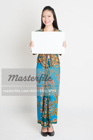 Full body portrait of Southeast Asian girl in batik dress hands holding white blank placard, standing on plain background. Stock Photo - Budget Royalty-Free, Image code: 400-08113793