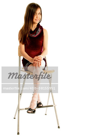 Attractive Teen Girl with Long Brown Hair in Purple Dress Sitting on Chair and Posing isolated on white background Stock Photo - Budget Royalty-Free, Image code: 400-08155951