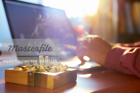 Close up of ashtray full of cigarette, with man in background working on laptop computer and smoking indoors on early morning. Concept of addiction and abuse of nicotine. Stock Photo - Budget Royalty-Free, Image code: 400-08223129