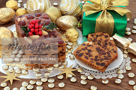 Genoa cake with gold christmas bauble decorations, holly and gift box over oak background. Stock Photo - Budget Royalty-Free, Image code: 400-08282494