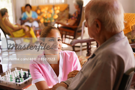 Old people in geriatric hospice: young attractive hispanic woman working as nurse takes care of a senior man on wheelchair. She talks with him then goes away to help other patients Stock Photo - Budget Royalty-Free, Image code: 400-08507323