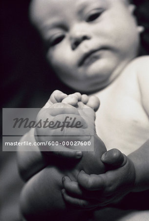 Baby Holding Foot Stock Photo - Premium Royalty-Free, Image code: 600-00027600