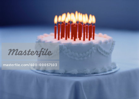 Cake with Lit Candles on Corner Of Table Stock Photo - Premium Royalty-Free, Image code: 600-00057103