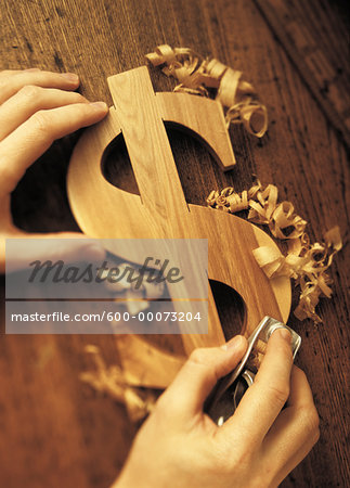 Close-Up of Hands Carving Wooden Dollar Sign Stock Photo - Premium Royalty-Free, Image code: 600-00073204