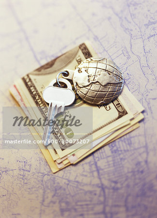 Key with Globe Keychain on Stack Of Currency on Map Stock Photo - Premium Royalty-Free, Image code: 600-00073207
