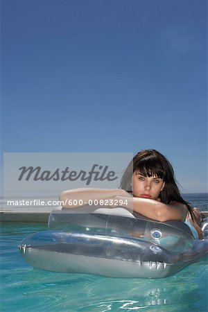 Woman Floating In Pool Stock Photo - Premium Royalty-Free, Image code: 600-00823294