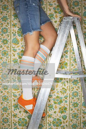 Woman Standing on Ladder Stock Photo - Premium Royalty-Free, Image code: 600-00824474