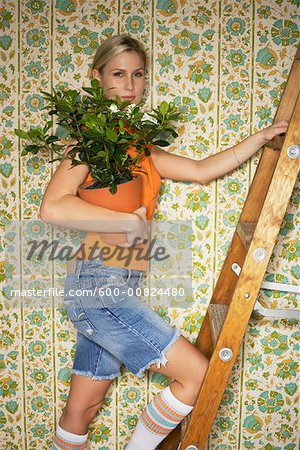 Woman Standing on Ladder, Holding Plant Stock Photo - Premium Royalty-Free, Image code: 600-00824480