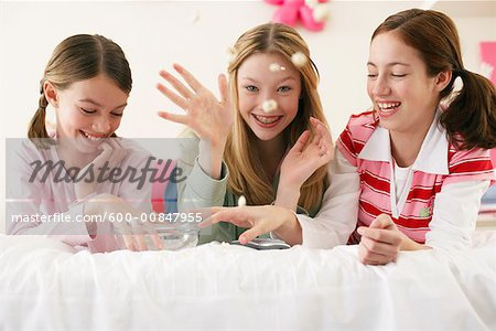 Girls Throwing Popcorn in Bedroom Stock Photo - Premium Royalty-Free, Image code: 600-00847955
