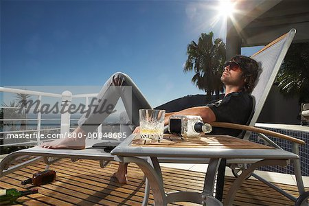 Man Sitting on Patio Chair Stock Photo - Premium Royalty-Free, Image code: 600-00848685