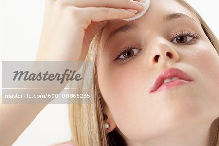 Girl Applying Make-Up Stock Photo - Premium Royalty-Free, Image code: 600-00866235