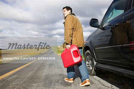 Man Carrying Gas Can on Country Road Stock Photo - Premium Royalty-Free, Image code: 600-00866958