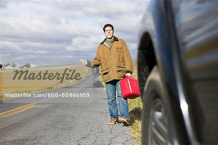 Man With Gas Can, Trying To Hitch a Ride Stock Photo - Premium Royalty-Free, Image code: 600-00866959