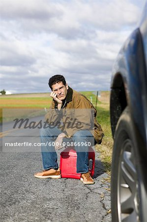 Man Sitting on Gas Can Stock Photo - Premium Royalty-Free, Image code: 600-00866960