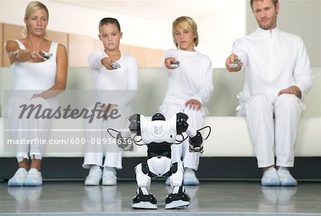 Portrait of Family Sitting on Sofa, Using Remote Controls on Robot Stock Photo - Premium Royalty-Free, Image code: 600-00934636