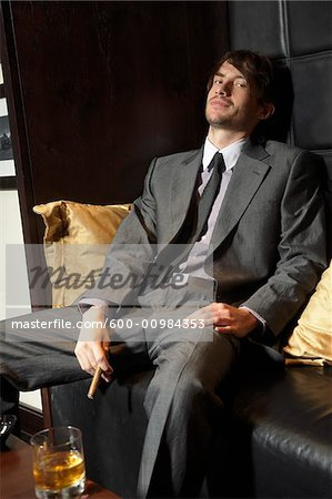 Man Sitting on Sofa with Cigar and Liquor Stock Photo - Premium Royalty-Free, Image code: 600-00984353