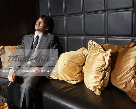 Man Relaxing on Sofa with Cigar and Liquor Stock Photo - Premium Royalty-Free, Image code: 600-00984354
