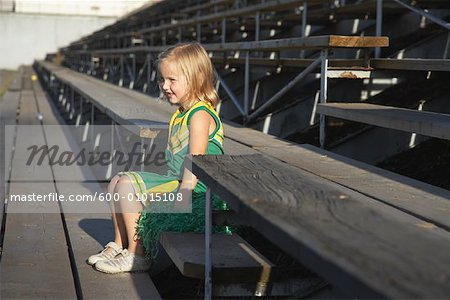 Girl Dressed as Cheerleader in Bleachers Stock Photo - Premium Royalty-Free, Image code: 600-01015108