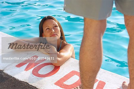Woman in Swimming Pool Looking up at Man Stock Photo - Premium Royalty-Free, Image code: 600-01041631