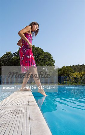 Woman at Side of Swimming Pool Stock Photo - Premium Royalty-Free, Image code: 600-01041644
