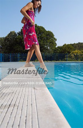 Woman at Side of Swimming Pool Stock Photo - Premium Royalty-Free, Image code: 600-01041645