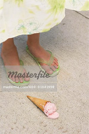 Close-up of Girl's Feet and Ice Cream Cone on Ground Stock Photo - Premium Royalty-Free, Image code: 600-01041998