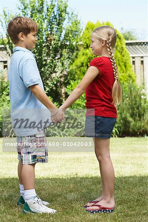 Sideview of Boy and Girl Standing in Backyard Holding Hands Stock Photo - Premium Royalty-Free, Image code: 600-01042003