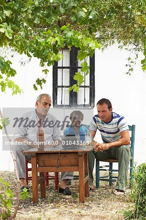 Grandfather, Father and Son Watching Television in Backyard Stock Photo - Premium Royalty-Free, Image code: 600-01043369