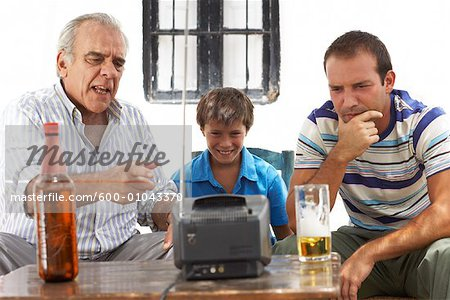 Grandfather, Father and Son Watching Television in Backyard Stock Photo - Premium Royalty-Free, Image code: 600-01043370