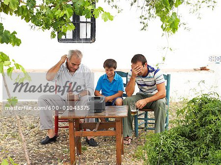Grandfather, Father and Son Watching Television in Backyard Stock Photo - Premium Royalty-Free, Image code: 600-01043375