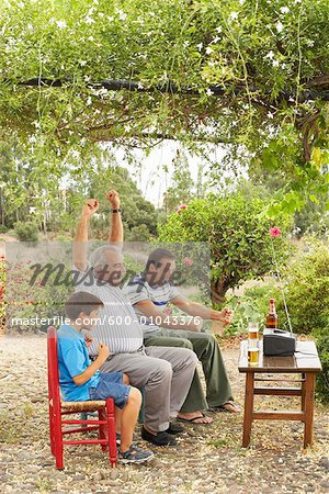 Grandfather, Father and Son Watching Television in Backyard Stock Photo - Premium Royalty-Free, Image code: 600-01043376