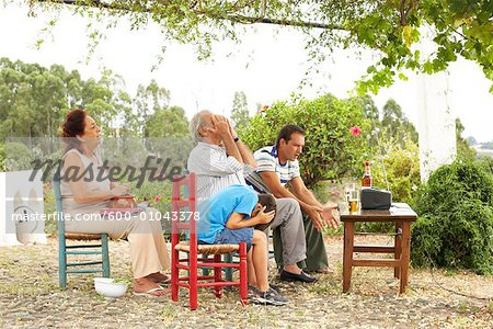 Grandfather, Grandmother, Father and Son Watching Television in Backyard Stock Photo - Premium Royalty-Free, Image code: 600-01043378