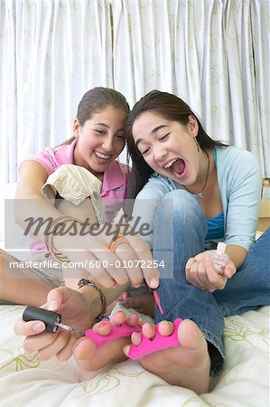 Girls Painting Toenails Together Stock Photo - Premium Royalty-Free, Image code: 600-01072254