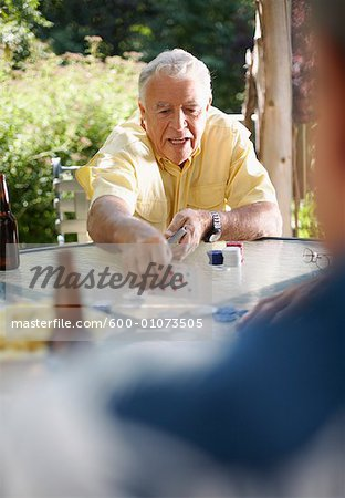 Man Playing Cards Outdoors Stock Photo - Premium Royalty-Free, Image code: 600-01073505