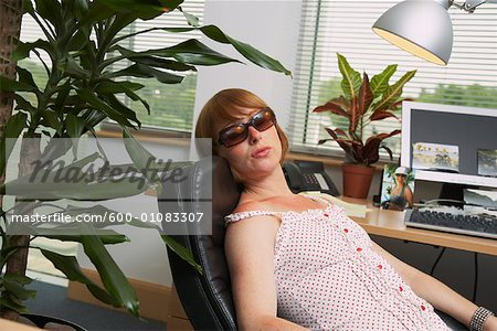Woman Suntanning under Office Lamp Stock Photo - Premium Royalty-Free, Image code: 600-01083307