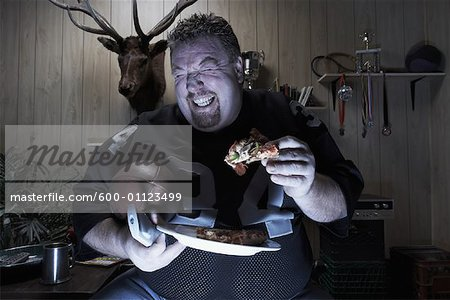 Man Watching TV and Eating Pizza Stock Photo - Premium Royalty-Free, Image code: 600-01123499