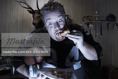 Man Watching TV and Eating Pizza Stock Photo - Premium Royalty-Free, Image code: 600-01123500